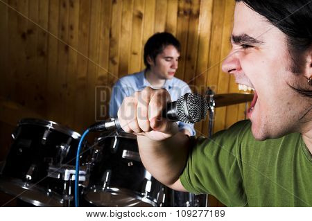 Microphone scream and Drummer playing behind in blur. Rock music concept
