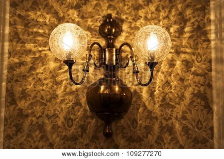 Old lamp on a wall with retro vintage wallpaper