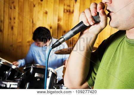 Microphone and Drummer playing behind in blur. Rock music concept