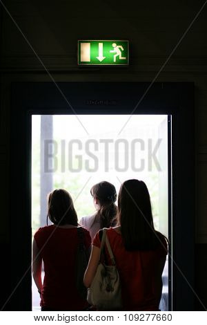 Three girls exit the building on exit door. Exit symbol