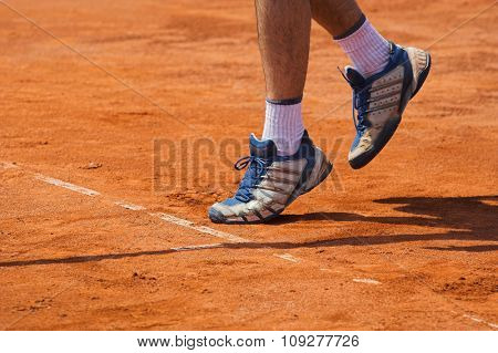Clay tennis court with Tennis player serving pose.