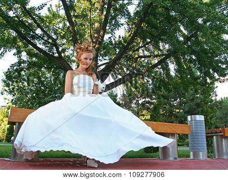 Wedding concept. Bride portrait in wedding dress sitting in park