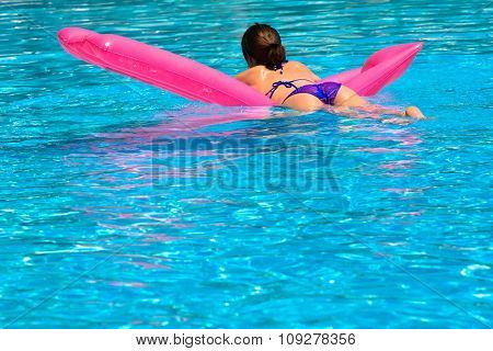 Young woman relaxing in pool and floating
