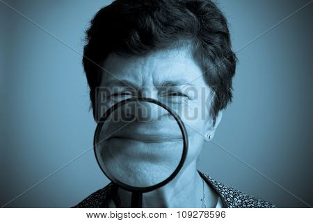 Woman and magnifier on her smile. Fake amused woman and psychology concept