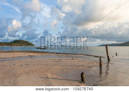 Sandy Beach And Going Fishing Boat During Sunset.