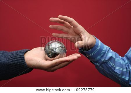 Hand grabbing a small planet puzzle globe. World concept