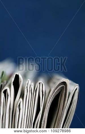 Stack of newspaper on blue background close up