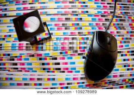 Computer mouse and printing loupe, focus on CMYK strips. Prepress color menagement in print production concept.