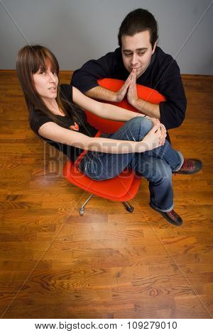 Man and woman sitting on red chair looking at camera and waiting. Wide angle lens distortion