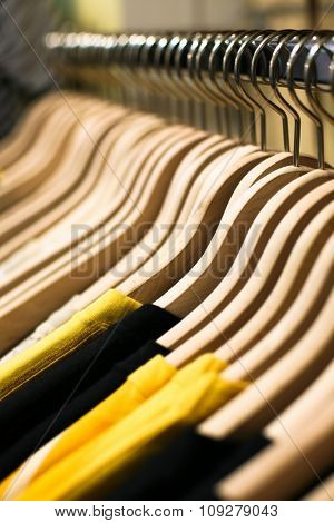 Clothes hangers with shirts in the fashion store. Clothes store concept