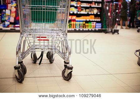Empty shopping cart in big store with products and few people in background. Shop concept