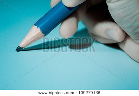 Big pencil in hand close up. Cool light with shadows, education concept