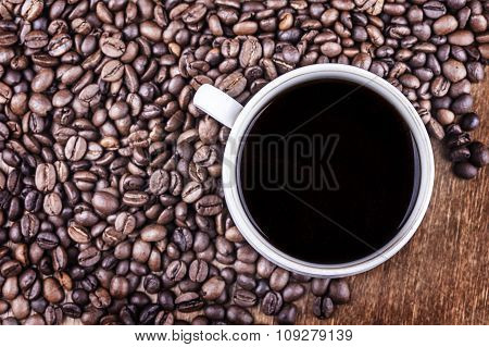 Coffee cup and coffee beans on table top view
