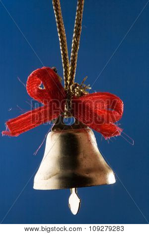 Golden Christmas bell with red ribbons isolated on blue close up