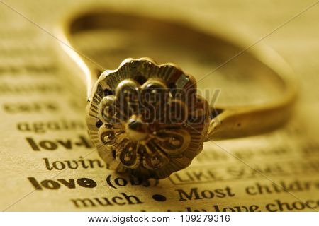 Engagement ring and love word on yellow light and soft background