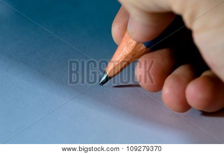 Big pencil in hand close up. Cool light with shadows