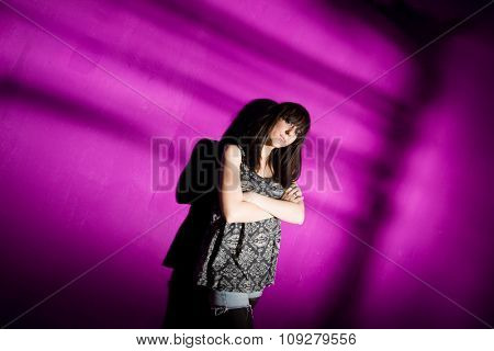 Worried young woman with arms crossed against pink wall with strong shadow. Sad girl in depression concept
