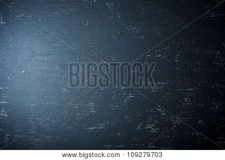 Blue spotlight light on black grunge wall. Can be used as background texture