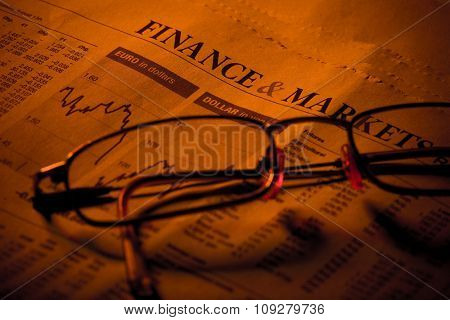 Business section in newspaper with currency graph and statistic under red light with glasses. Focus on headline FINANCE