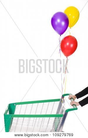 Woman hands push shopping trolley with  helium balloons