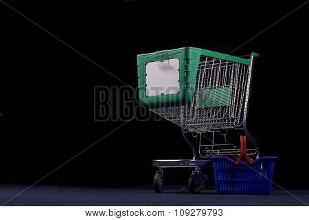 Big shopping cart - trolley and small basket in dark. Supermarket concept