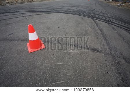 Orange traffic cone and round car drift skid marks