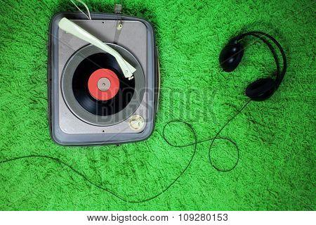 DJ tools: headphones and vintage turntable on funky carpet