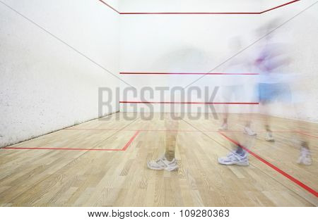 Two squash players in motion blur playing