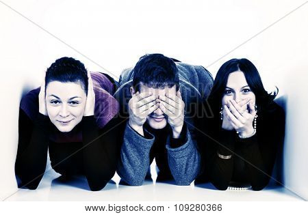 Three young people in small space covering ears, mouth and eyes. communication concept