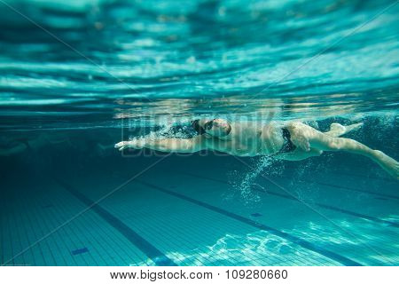 Swimmer swimming  in the pool. Underwater hi res photo.