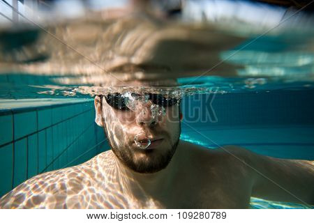 Underwater man portrait with swimming goggles and air bubbles in pool