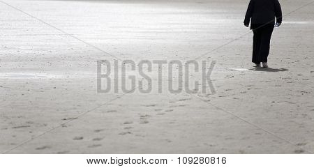 Woman walking on sand beach in early spring