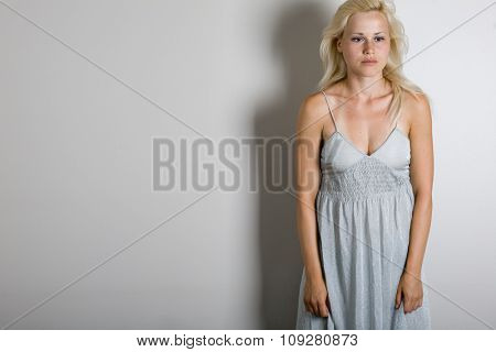 Sad beautiful woman on white wall standing. Sun bathing marks visible