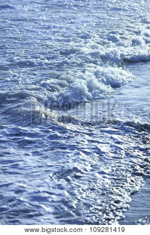 Background of a surface of water. Waves along the beach