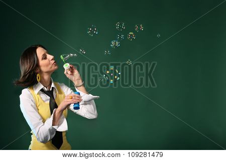 Woman making soap bubbles on green background with copy space. Happy lifestyle concept
