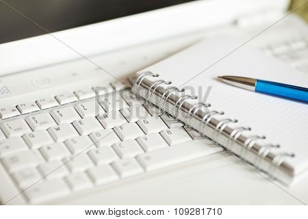 Modern journalist tools, white laptop, notebook and a pen. Shallow depth of field, focus on binding
