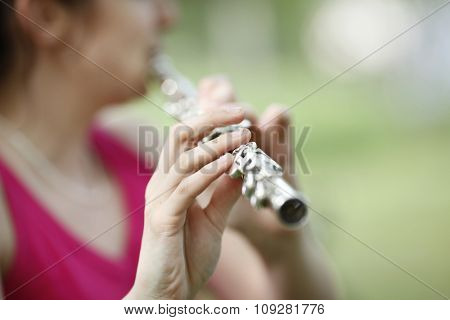 Young woman playing classic flute in nature in background. Shallow DOF