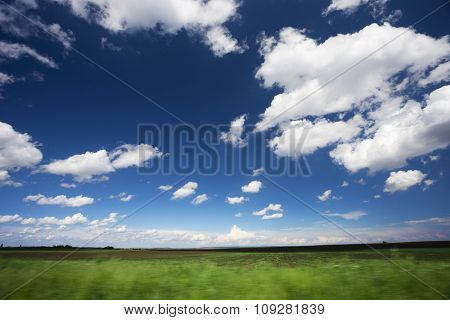 Green field and blue sky with white clouds. Motion blur visible in front