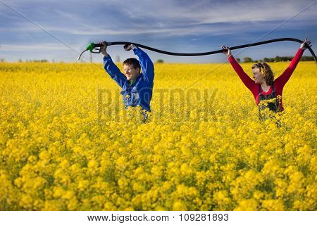Eco fuel concept: young people holding gas station nozzle hose  in a yellow field