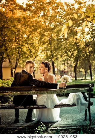 Romantic wedding couple sitting on a bench in the park
