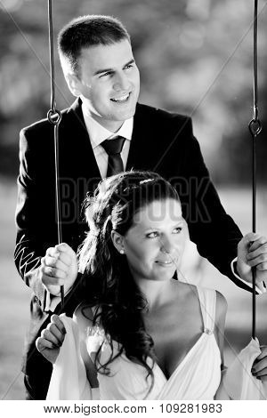 Romantic wedding couple. Husband swinging his wife on the swing