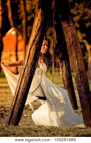 Romantic wedding concept. Bride swinging on the swing