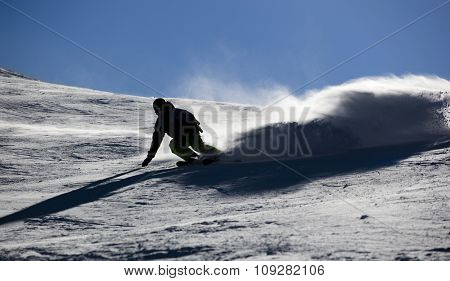 Backlit skier splashing snow powder while turning and skiing fast