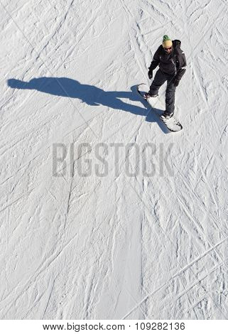 Snowboarder from above on a snow slope riding his snowboard.