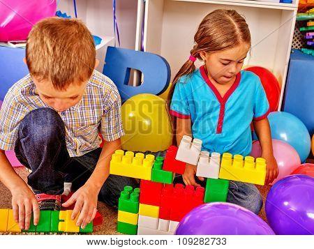 Couple children game blocks on floor in kindergarten .