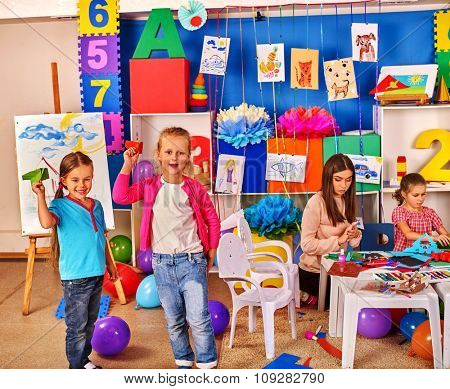 Group kids holding colored paper on table in kindergarten interior.