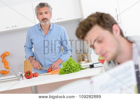 Man preparing vegetables, looking forward at younger man's book