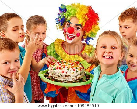 Clown male in costume holding cake on birthday with group children. Isolated.