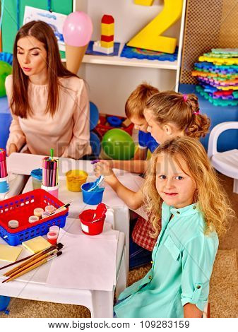 Children with young woman painting on paper at table  in  kindergarten .