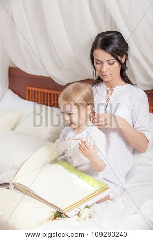 Happy mother and kid daughter read a book together in bed